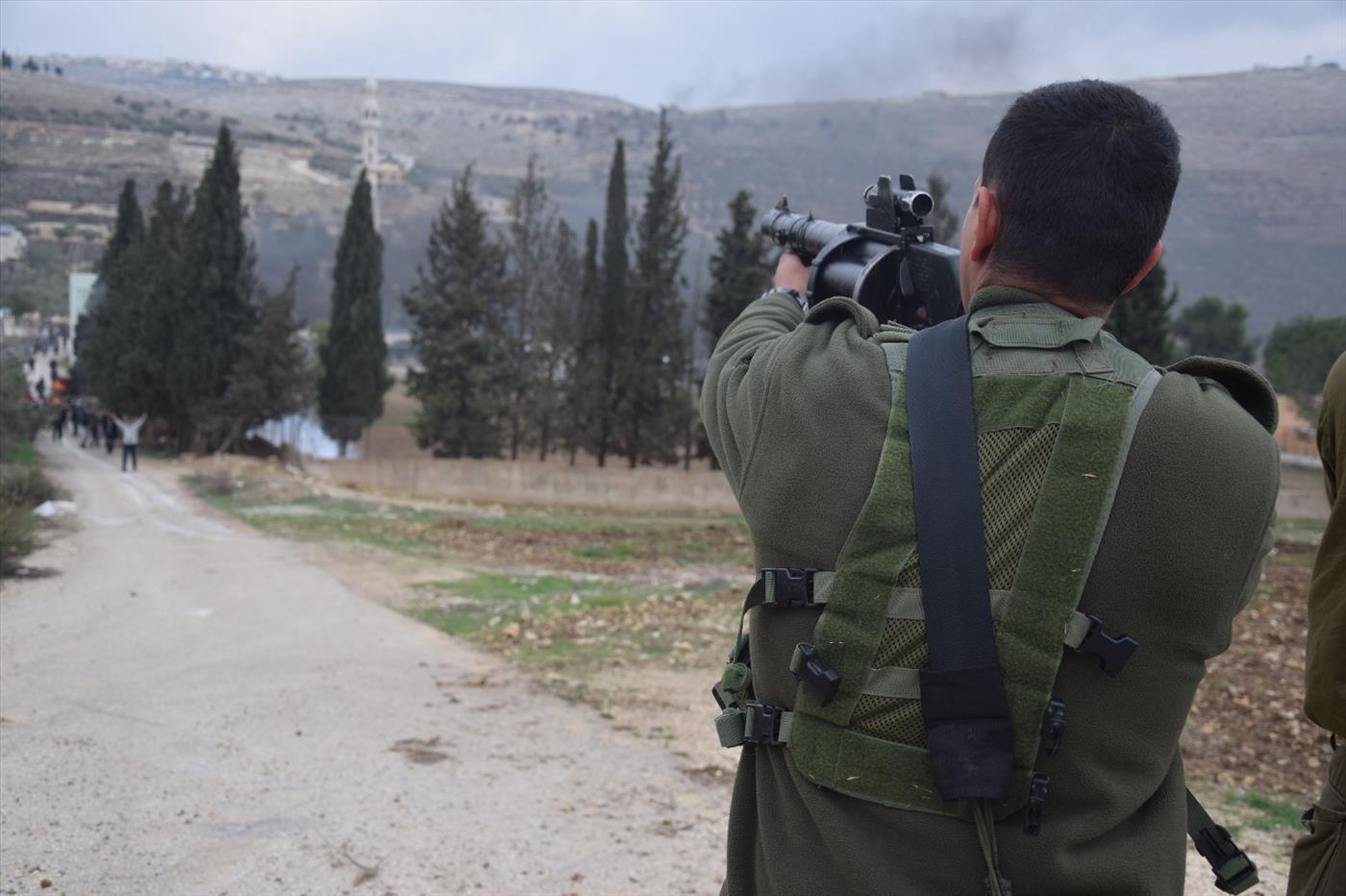 חייל יורה לעבר הפורעים (צילום: אברהם שפירא)