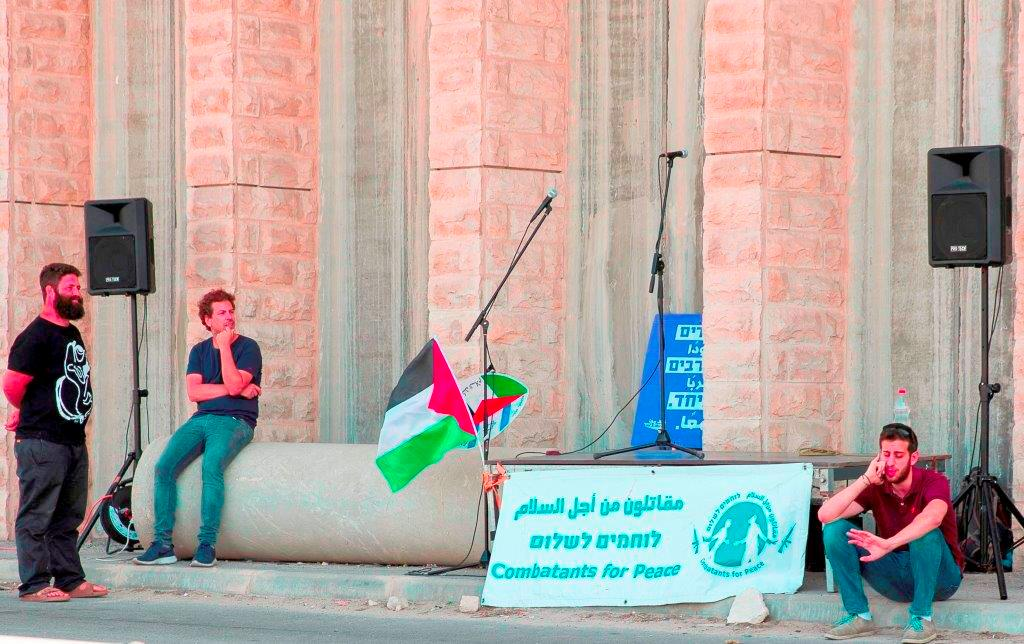 """שלט של תנועת """"עומדים ביחד"""" (במרכז התמונה) במחאת אנרכיסטים ופעילי שמאל בגוש עציון. ארכיון (שירה הרשקופ TPS)"""