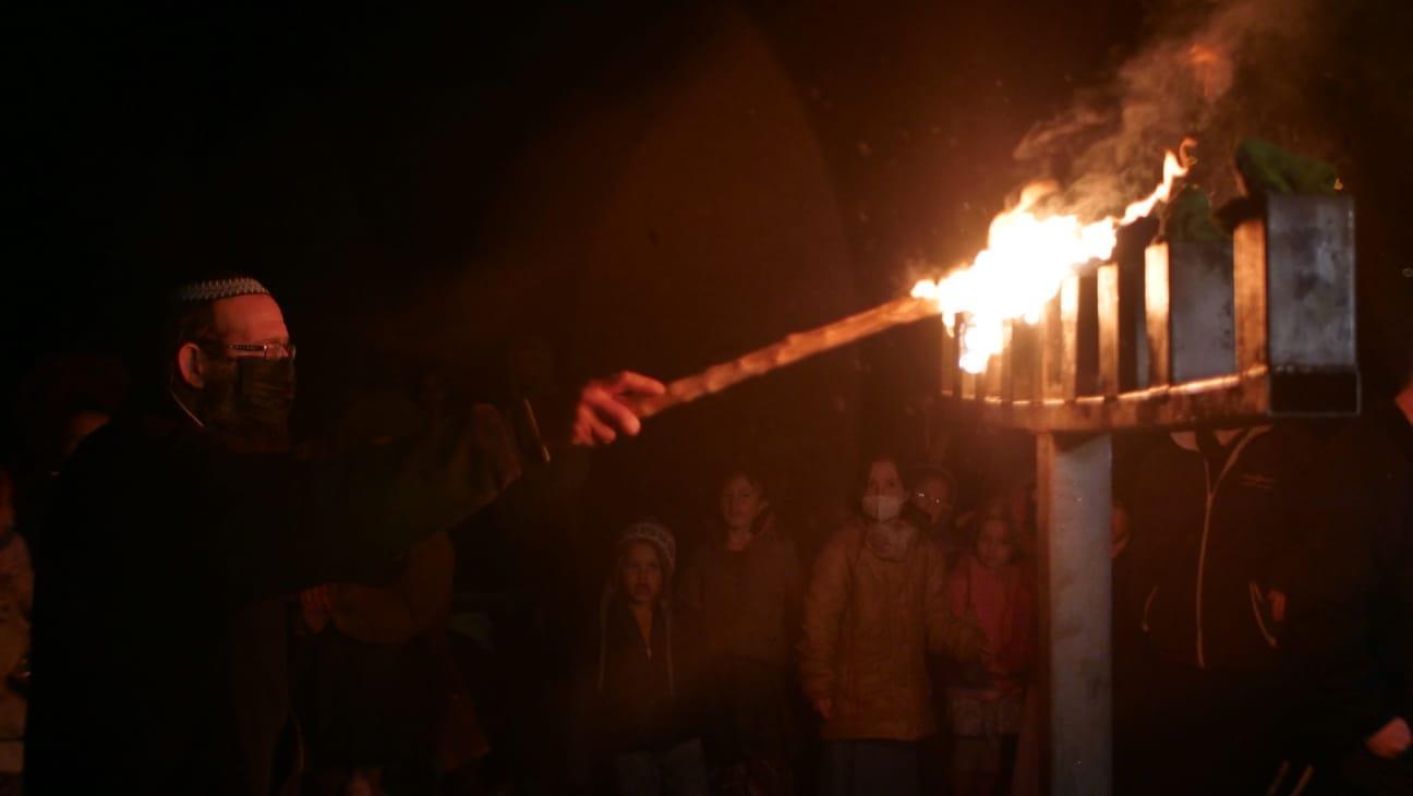 """הדלקת נר חנוכה בכניסה לשכונת קומי אורי בידי יו""""ר מזכירות יצהר (אברהם שפירא)"""