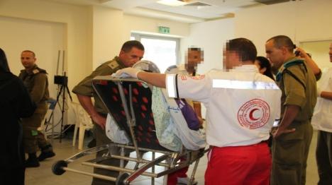 """קציני צה""""ל עם מטופלת ערביה במעבר ארז. ארכיון דובר צה""""ל"""